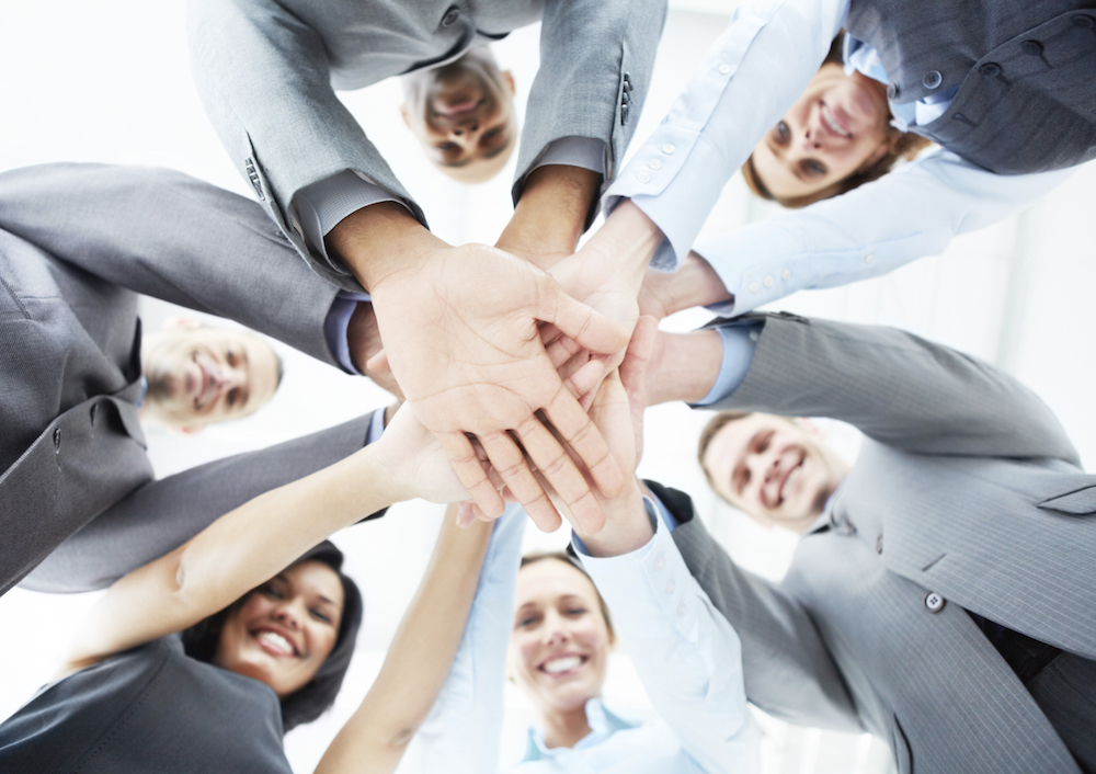 A low-angle view of a smiling business team standing with their hands piled up together - portrait
